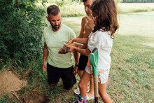 Father And Two Kids Burying The Family Pet.