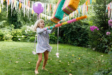 A Birthday Girl In The Garden  With Rainbow Pinata