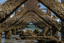 View Under At Broken Old Structure Remains Of Pier In The Sea. Small Wave Crashing Into The Textured Rusty Pier Posts.