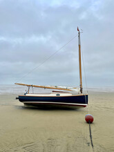 Small Sailboat Beached At Low Tide
