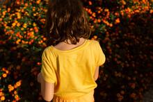Back Of Kid In Yellow Over Flowery Orange Bush