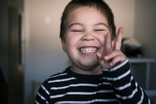 Happy Mixed Asian Toddler Boy Giving The Peace Sign