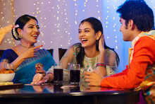 Family Members Having Fun While Playing Cards On Dining Table On The Occasion Of Diwali