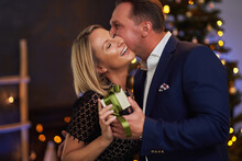 Couple Kiss In Front Of Chrismas Tree Holding Gift