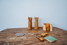 Two Homemade Toy Cats Stand On The Work Surface. Toys Are Made Of Wood, Around Lie Tools For Carving Wood And Lying Sawdust. Creative Pursuits, Wood Carving.