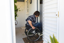Caucasian Disabled Young Man Sitting On Wheelchair Entering His House Though The Door
