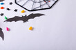 Leinwandbild Motiv Composition of halloween decorations with spider web, bats and sweets with copy space on white