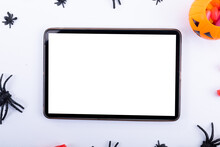 Composition Of Halloween Spiders, Pumpkin And Sweets And Tablet With Copy Space On White Background