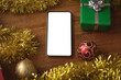 Leinwandbild Motiv Smartphone with copy space, christmas gifts and decorations on wooden table