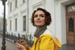 canvas print picture - Woman in yellow raincoat with smartphone in hand
