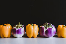 Fresh Yellow Peppers And Eggplants In Line On Table On Black Background