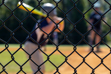 Little League Batter Out Of Focus In The Background While The Backstop Is In Focus