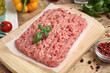 Leinwandbild Motiv Raw chicken minced meat with basil and spices on wooden table, closeup