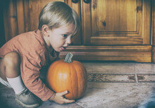 Beautiful And Smiling Baby Playing With Halloween Decoration At Home. Caucasian Little Boy Playing With A Pumpkin. My First Halloween.  Rustic Wood Background