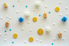 """Wooden Dreidels, Six Pointed Star Candles, Chocolate Coins For Jewish Holiday Hanukkah On White Background. Hebrew Letters On Dreidels Say: """"Great Miracle Happened Here""""."""