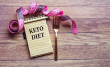 Keto Diet Concept With Notebook,  Fork And Pink Measuring Tape On A Wooden Background