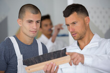 Two Men Inspecting A Brush