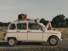 Hippie Lying On Old Timer Car In Countryside
