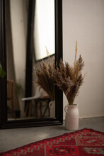 Dried Flowers In A Large Vase Next To A Red Carpet And A Mirror