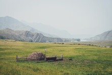 Beautiful Foggy Mountain Landscape With Scarecrow On Wooden Fence Around Haystack On Background Of Mountains And Rocks Silhouettes In Fog. Stack Of Hay Is Surrounded By Wood Fence In Vintage Tones.