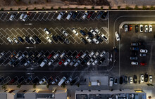 Drone Aerial View Of Parking Lots With Cars At Night. Crowded Shopping Mall Car Park.