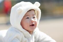 屋外で白いベビー服を着て笑っている赤ちゃん