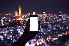 スマートフォン携帯と東京の夜景