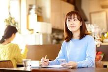 カフェで携帯電話を見ながらスケジュール帳を確認する女性