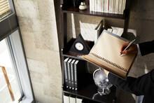 本棚の前でノートに書いているビジネスマンの手元