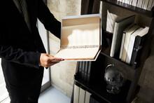 本棚の前でファイルを広げているビジネスマンの手元