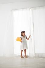 窓の前でオレンジ色のフーセンを手に持つ女の子