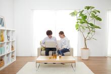 リビングのソファーに座りノートパソコンを見る男女