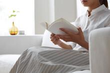 明るい窓際のソファーで本を見る女性