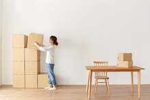 積まれたダンボール箱とテーブルと、箱を運ぶ女性