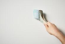 ハケでペンキを塗る女性の手