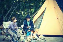 テントの前でたき火をする二人