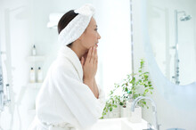 洗面台の鏡を見てお化粧をする女性