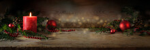 Atmospheric Advent And Christmas Decoration With A Lit Red Candle, Balls And Evergreen Yew Branches On Dark Rustic Wooden Planks, Wide Panoramic Format, Copy Space