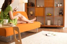 ソファで足にクリームを塗る女性