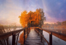 Small Wooden House On Island With A Wooden Pier In The Middle Of A Lake At Foggy Autumn Morning During Sunrise. Fairy Landscape At Fall.
