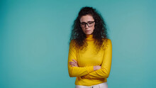 Upset Young Woman In Glasses And Turtleneck Standing With Crossed Arms Isolated On Blue