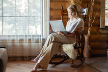 A Blonde Woman In Beige Home Clothes Sits In A Rocking Chair With A Laptop In Her Hands In A Cozy Room With Large Windows And Wooden Walls. Freelancing And Distance Learning.