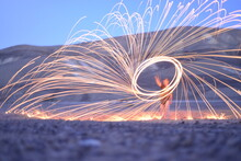 Iron Wool Circle Drawing Light Fireworks. Burning Steel Wool Spinning, Trajectories Of Burning Sparks At Night. Movement Light Effect, Steel Wool Fire Hoop. Long Exposure Light Painting, Pyrotechnic