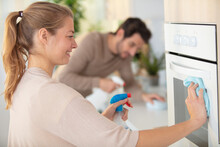Young Woman Cleaning Oven With Spray And Rug