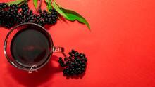 Top View Of A Mug Of Red Tea. Herbal Tea, Medicinal From Black Elderberry Berries. Homeopathy Herbal Tincture