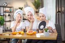 Two Caucasian Sisters And Their Mother With Towels On Heads Doing Face Procedures While Sitting Together At Table. Caring Mother Teaching Pretty Daughters Various Beauty Tricks At Home.