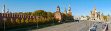 Panoramic View Of The Kremlin From The Moskvoretsky Bridge Against The Background Of The Blue Sky. People Walk Along Red Square. Moscow, Russia.