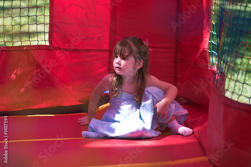 Fotografia young girl sitting in an inflatable bouncy