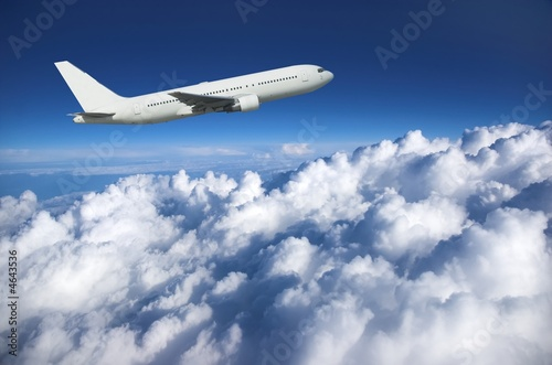 Photo Large airliner along clouds