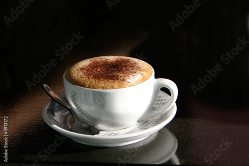A cappuccino in a cup on a black table Fototapete